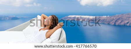 Relaxing woman sleeping on outdoor daybed patio furniture enjoying view of Mediterranean sea Europe travel destination. Asian girl lying down on pillows dreaming carefree happy. Luxury home living. - stock photo