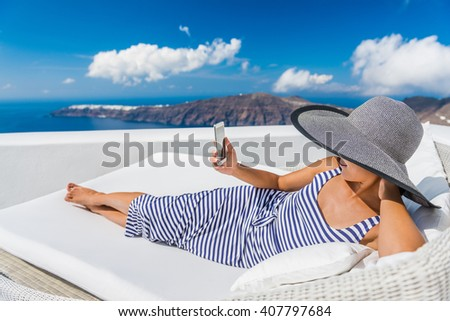Relaxing woman using smart phone while lying on couch outdoor. Beautiful female is at resort terrace. Happy tourist is spending leisure time during vacation on Santorini, Greece, Europe.