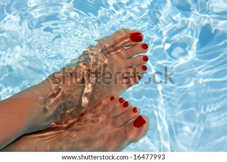 Relaxing woman with his foot on the water - stock photo