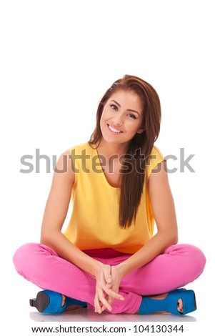 Relaxing young casual woman sitting on floor isolated on white background - stock photo