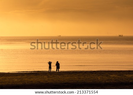 Relaxing young couple silhouette. woman walking by a pathway on a beach - stock photo
