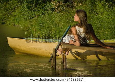 Relaxing young woman on wooden pier at the lake in summer day  - stock photo
