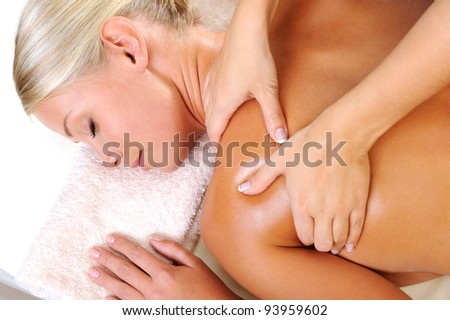 Relaxing young woman taking massage in beauty salon - stock photo
