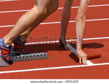 Relay runner in starting blocks ready for the start with baton in hand