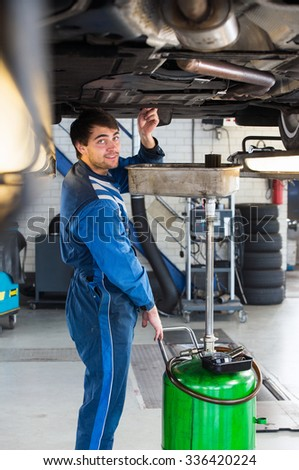 Reliable looking mechanic, checking the oil of a car on a car lift in a garage - stock photo