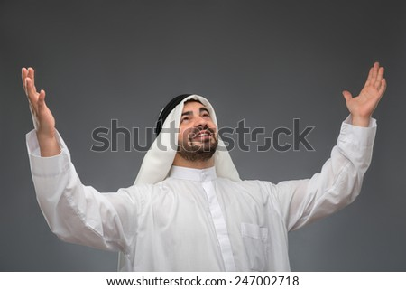 Relieved businessman. Young handsome Arabic business man raising his hands with his eyes up and laughing while standing against grey background - stock photo