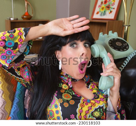 Relieved woman in paisley on rotary telephone