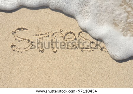 Relieving Stress, the Word Stress Being Washed Away by a Wave on a Beach - stock photo
