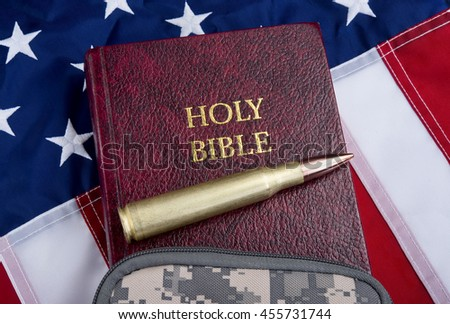 Religion and peace with fifty caliber bullet , bible and American flag . - stock photo