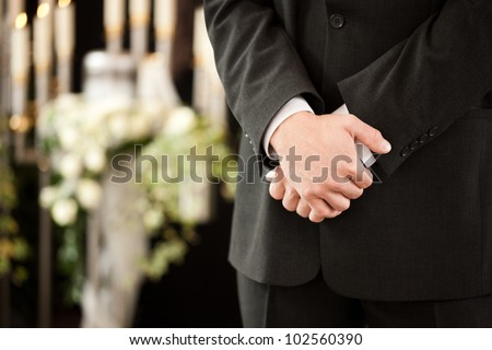 Religion, death and dolor  - undertaker at funeral standing in front or urn - stock photo
