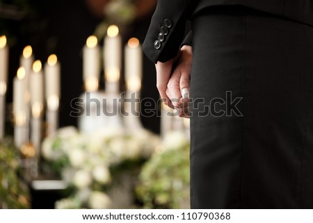 Religion, death and dolor  - woman at urn funeral mourning the death of a loved person - stock photo