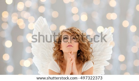 religion, faith, christmas, holidays and people concept - praying teenage girl or young woman with angel wings over lights background