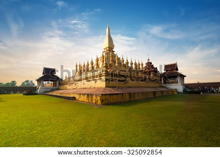 Religious architecture and landmarks. Golden buddhist pagoda of Phra That Luang Temple under sunset sky. Vientiane, Laos travel landscape and destinations - stock photo