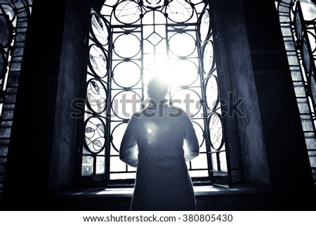 Religious christian woman looking trough the stained glass church window light.Woman praying to god at St. Alexander Nevsky Cathedral.Finding serenity in religion,faith and hope concept.Enlightenment - stock photo