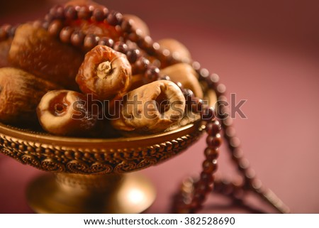 Religious food and objects. Close up of arabic dates and rosary. - stock photo