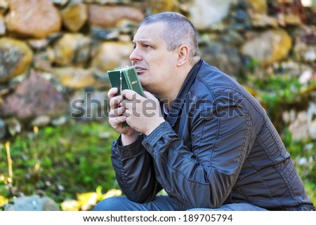 Religious man with Holy Bible and Rosary at place of worship - stock photo