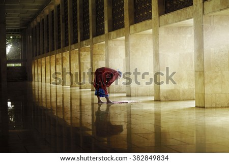 Religious muslim man praying inside the mosque - stock photo