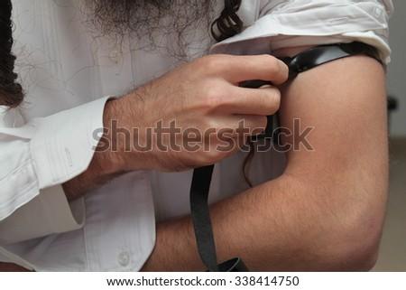 religious orthodox Jew with arm-tefillin  - stock photo