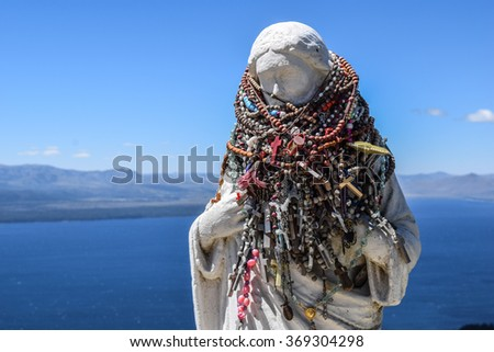 Religious statue wrapped in rosaries - stock photo
