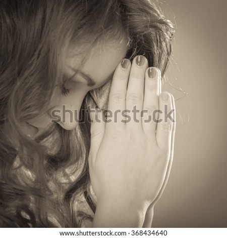 Religious woman praying to god jesus christ. Strong christian religion faith. Christianity. Sepia filter. - stock photo