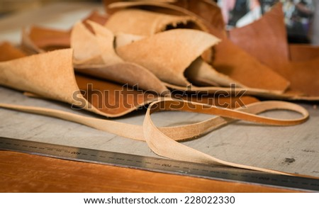 Remainders of the leather on the working desk in the leather workshop. Low depth of field. - stock photo