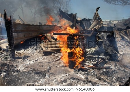 Remains of a burnt informal dwelling or shack house with a chair still burning