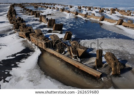 remains of a wooden pier on the lake in winter, landscape - stock photo