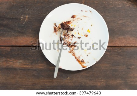 Remains of delicious cake on white plate with fork. Selective focus. - stock photo