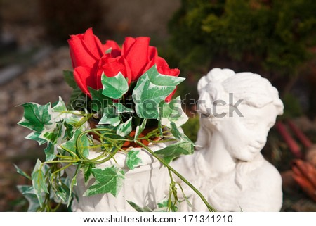 Remember with roses - Statue with roses in the garden - stock photo