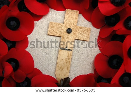 Remembrance Day Cross Surrounded by Poppies Remembrance Day cross centered in a wreath of red poppies.  Taken on a World War One Somme memorial. - stock photo