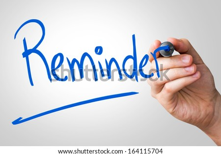 Reminder hand writing with a blue mark on a transparent board - stock photo