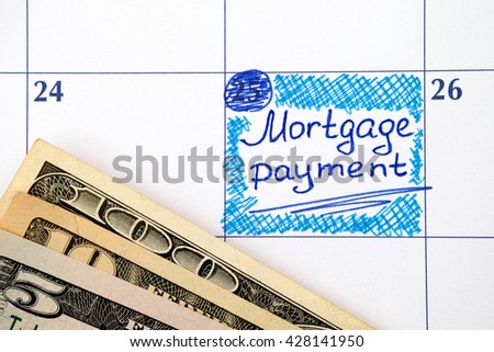 Reminder Mortgage Payment in calendar with dollar banknotes - stock photo