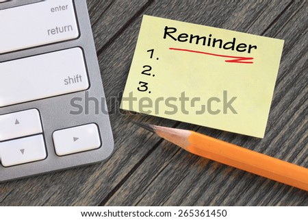 reminder note with desk background - stock photo