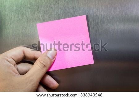 Reminder sticky note on refrigerator door - stock photo
