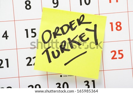 Reminder to Order a Turkey in time for Christmas dinner written on a yellow sticky paper note stuck to a wall calendar background - stock photo