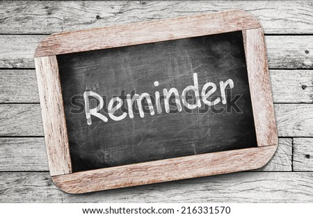 Reminder written on chalkboard - stock photo