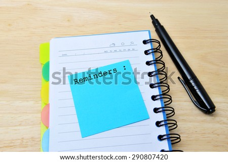 Reminders words written on a blue sticky note pinned, notebook with pan on wooden background - stock photo