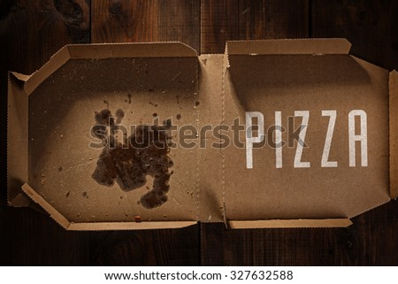 remnants of pizza in delivery box with pizza text on the wood - stock photo