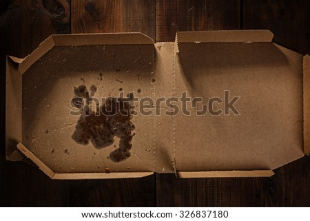 remnants of pizza in delivery box with pizza text you can put your writing on the box on the wood - stock photo
