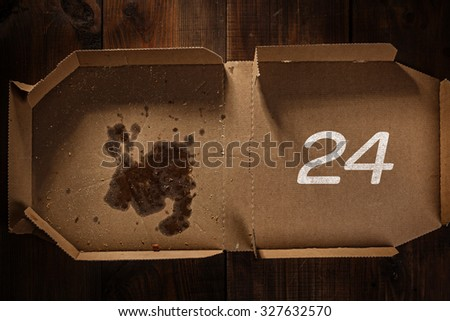 remnants of pizza in delivery box with 24 time text on the wood - stock photo