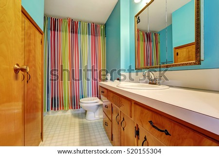 Remodeled bathroom interior with colorful shower curtain and blue walls. Northwest, USA