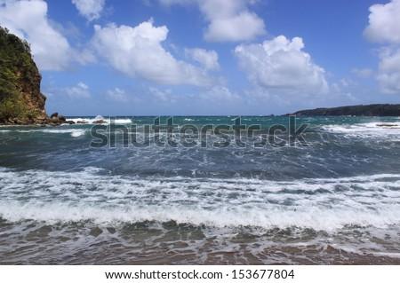 Remote black sand beach and blue sky. Atlantic Ocean, Dominica, Caribbean Islands - stock photo