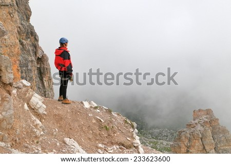 Remote climber standing under dark clouds on a mountain ledge, Dolomite Alps, Italy - stock photo
