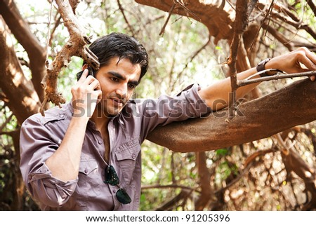 remote connectivity, man standing in the jungle and talking on mobile phone - stock photo