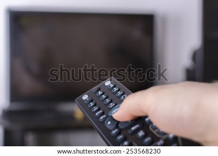 Remote control and TV - stock photo