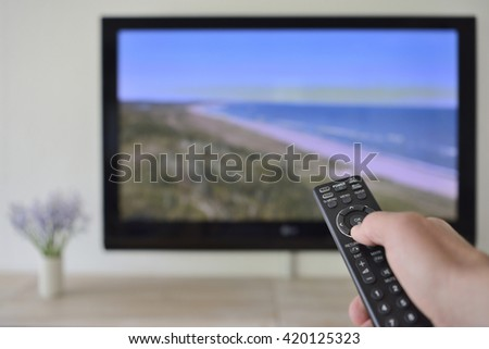 Remote Control in hand with Beach  on Screen