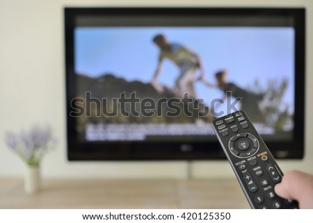 Remote Control in hand with outdoor people on Screen