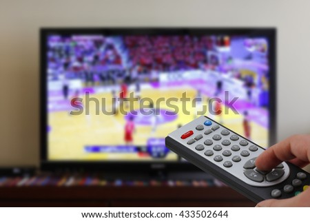 Remote control in the hand, during a basket match, sports