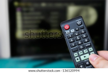 Remote control, TV in background - stock photo