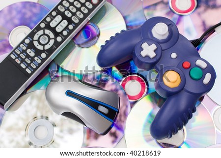 Remote control wireless computer mouse and video game controller over a bed of dvd disks isolated over white. - stock photo